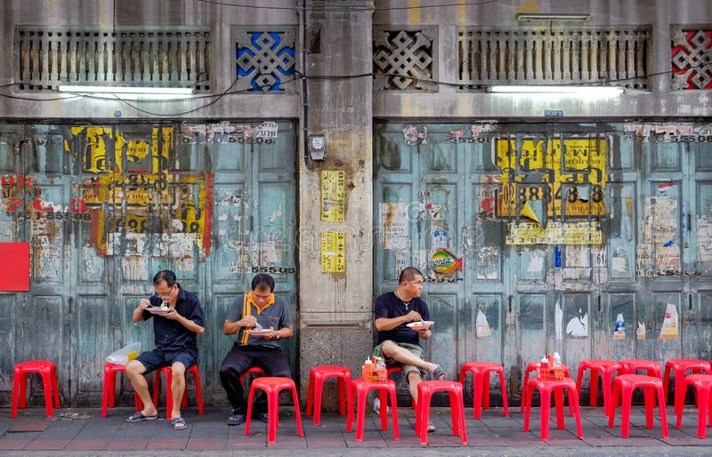 Unidentified Thai Asian people who` re sit on red chair for eating curry rice street food on footpat. Bangkok-Thailand JUL 6 2017: Unidentified Thai Asian people stock photo