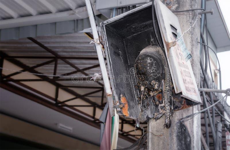 BANGKOK THAILAND - 15. JULI: Das verkohlte elektrische Meter, das MEA gehört, verließ auf elektrischem Pfosten auf Phasi Charoen  stockfoto