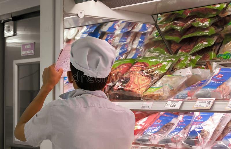 BANGKOK THAILAND - JULI 16: Supermarketdeltagaren kontrollerar inventarium på det kylde avsnittet av den Foodland supermarket in arkivbilder