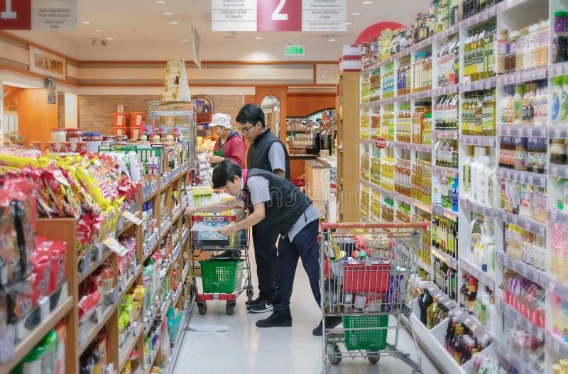 BANGKOK THAILAND - JULI 13: Unnamed inventarium för anställdkontrolllager på hyllorna av den Foodland supermarket i Victoria träd royaltyfri fotografi