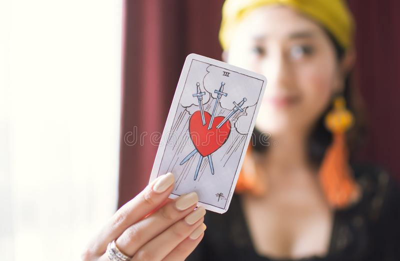 Closeup to a tarot card of heart stabbed by three swords stock images