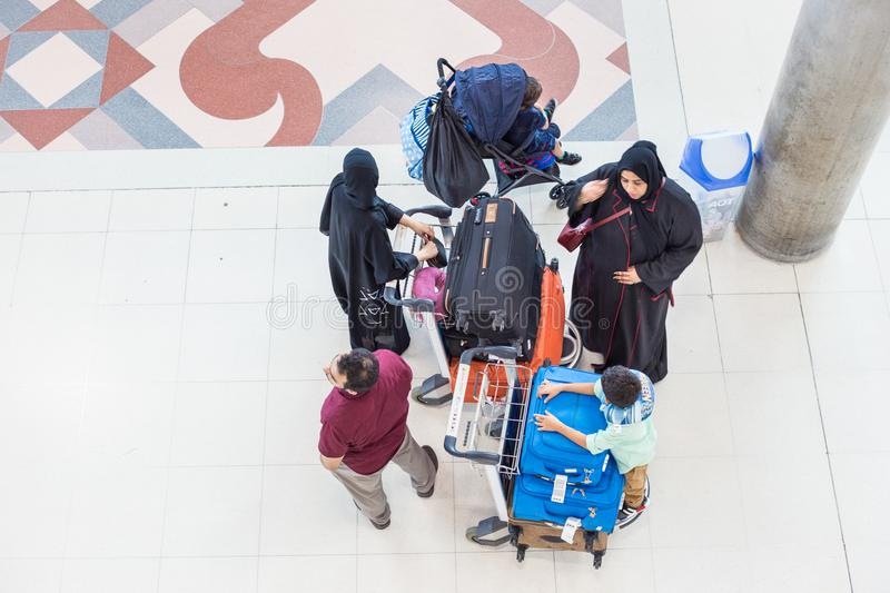 A group of middle east family wait at the airport with their lug. BANGKOK, THAILAND - 21 JULY 2018 - A group of middle east family wait at the airport with their royalty free stock image