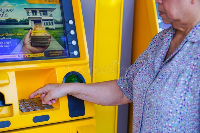 Bangkok, Thailand - June 20, 2018 : Asian senior or elderly old lady woman entering press button number code on machine stock photos
