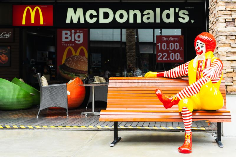 BANGKOK, THAILAND - 2019 JUNE 16: Ronald McDonald character sitting on bench, in front of McDonalds restaurant. Ronald McDonald is royalty free stock photography