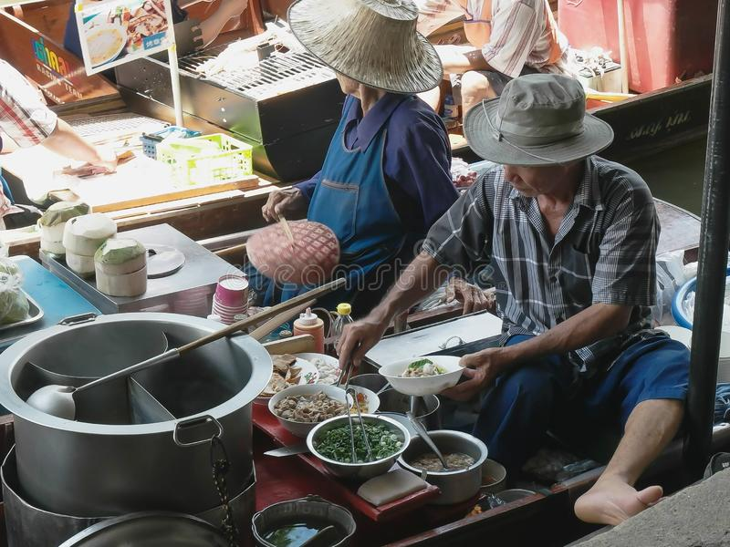 BANGKOK, THAILAND- JUNE, 23, 2017: a thai man cook serves food from a boat at damnoen saduak floating marke royalty free stock images