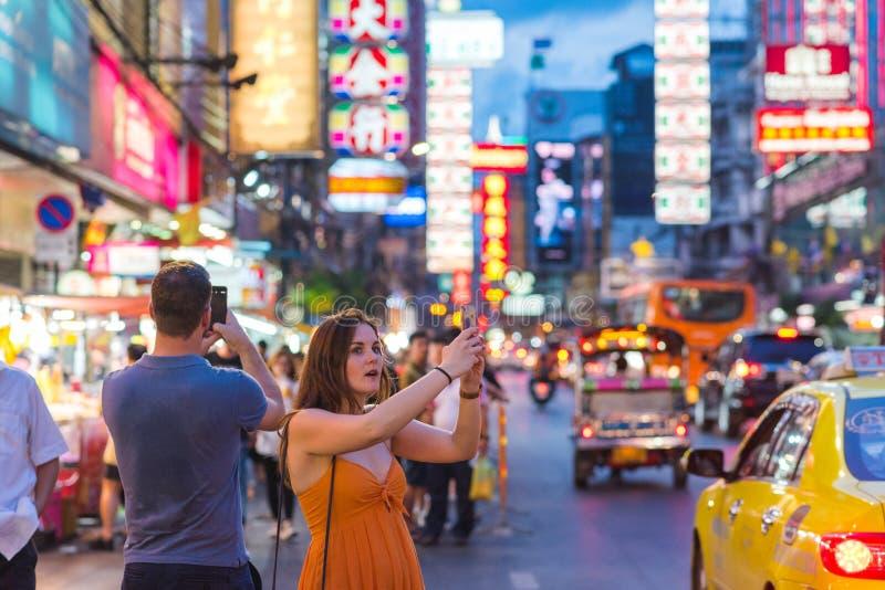 Bangkok, Thailand: two admiring travelers in Yaowarat Road, Chinatown at night royalty free stock photos