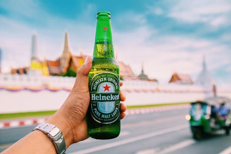 Bangkok, Thailand - Juni 2019: übergebene Flasche kaltes Heineken-Bier auf thailändischem Tempelpalast stockfotografie