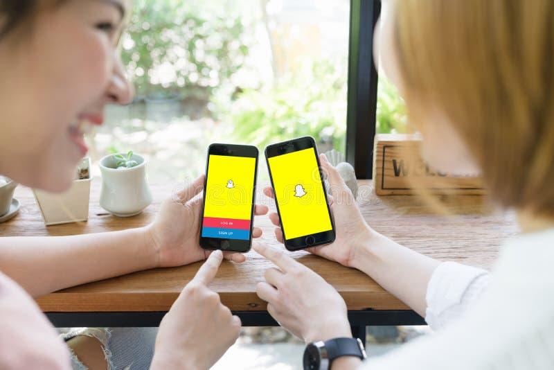 BANGKOK THAILAND - JUNI 04,2018: Kvinna för två asiat som använder snapchatapplikation på iphone Snapchat är online-socialt knyta royaltyfri bild