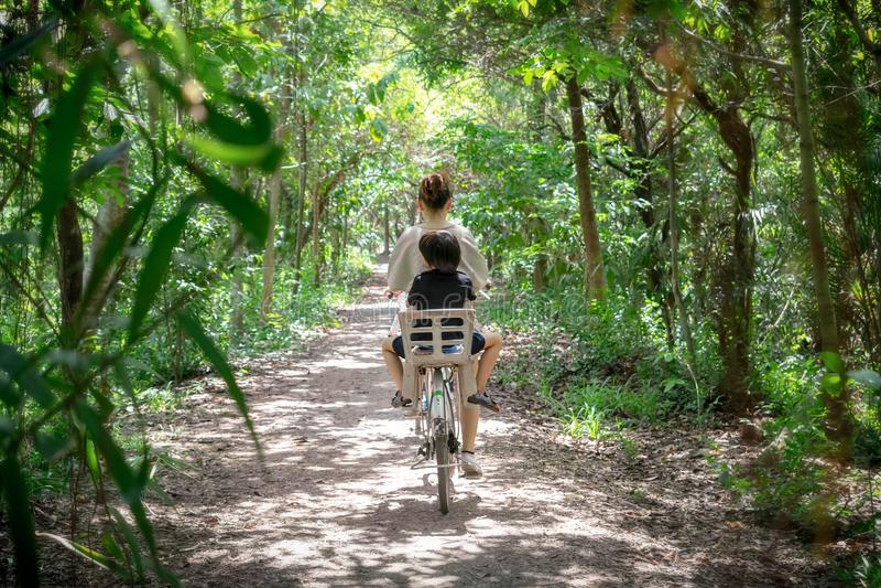 BANGKOK, THAILAND - 15. JUNI: Ungenannte Mutter und Sohn fährt Fahrrad durch den Erdweg in Sri Nakhon Khuean Khan Park herein lizenzfreie stockbilder