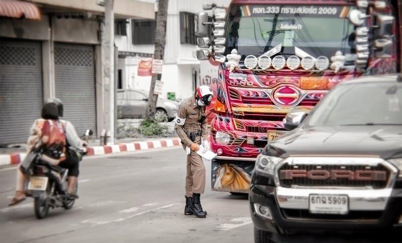 BANGKOK THAILAND - JUNI 12: Unnamed frågor för trafikpolis en biljett till den oidentifierade trafiklagbrytaren på den Petchkasem arkivfoto