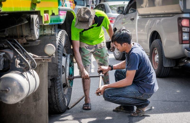 BANGKOK THAILAND - JUNI 15: Unnamed lastbilsförare drar åt hjulsläpanden efter ändrande hjul på vägsidan i Juni 15, 2019 royaltyfria bilder