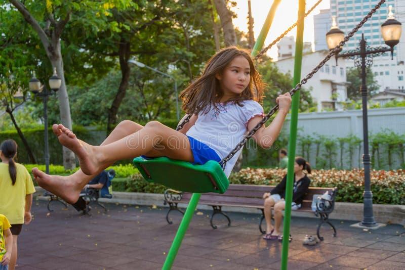Kinderwohlfahrt. Nettes thailändisches Mädchen, das ein Schwingen spielt stockbild