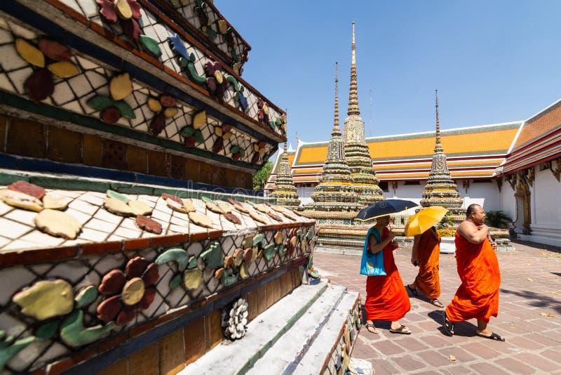BANGKOK, THAILAND - MAART 2019: boeddhistische monniken die langs reuzestupas van het Doen leunen van de Tempel van Boedha lopen stock afbeeldingen