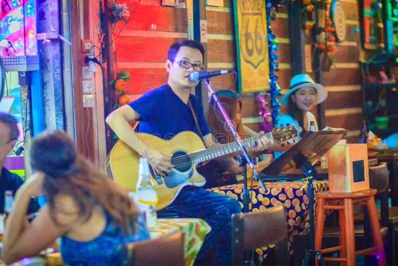 Bangkok, Thailand - Maart 2, 2017: Modieuze gitarist die zingen stock afbeelding