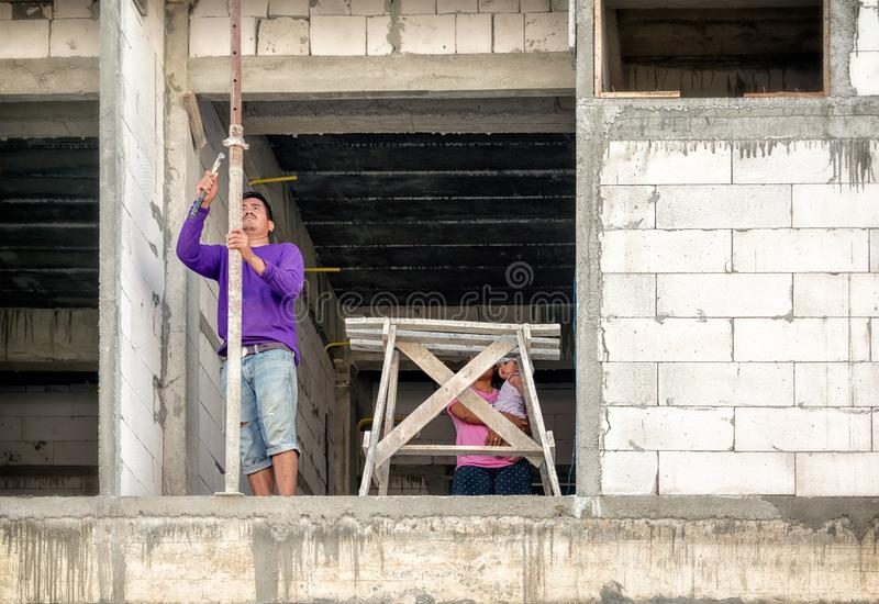 BANGKOK THAILAND - MAJ 05: Den oidentifierade byggnadsarbetaren kommer med frun och behandla som ett barn f?r att arbeta p? l?gen royaltyfri fotografi