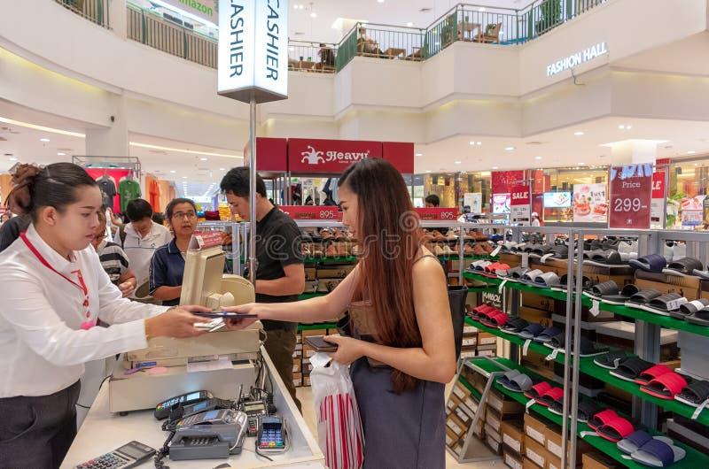 BANGKOK THAILAND - MAJ 20: Den oidentifierade kvinnliga kunden betalar för ett produktköp på kassörskan på en försäljning i galle royaltyfri fotografi