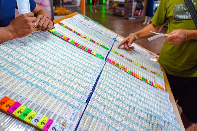 Bangkok Thailand - 27 Maj 2018: Det thailändska folket har gyckel som köper lotterit på framdelen av lotterikiosket på det Bangko fotografering för bildbyråer