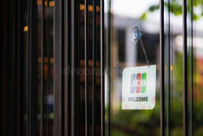 Bangkok Thailand - Maj 26, 2019: Hängningar för JCB-kreditkortar och för välkommet tecken framme av ett shoppa lager in i Bangkok royaltyfri fotografi