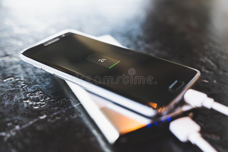 Bangkok Thailand - Maj 24, 2018: Makt för uppladdning för smartphone för kant för Samsung galax S7 via powerbankbatteriuppladdare royaltyfri bild