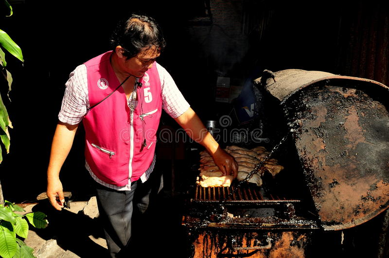 Bangkok, Thailand: Man Grilling Chicken. Thai cook grilling chicken pieces on a large cast-iron barbecue grill at his restaurant on a small soi off Lang Suan royalty free stock photography