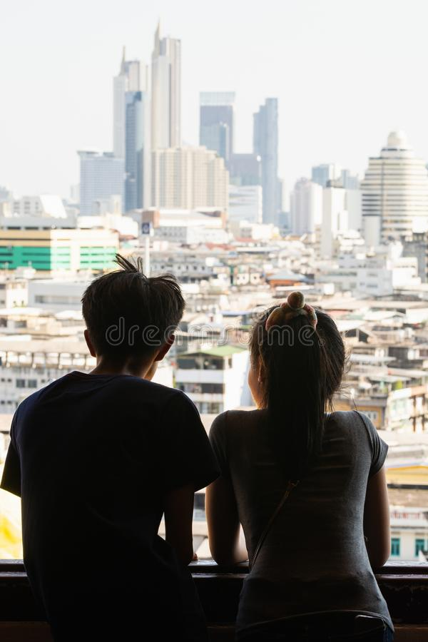 Bangkok, Thailand - March 2019: Asian couple looking out of Golden Mount Wat Saket temple window over royalty free stock photo