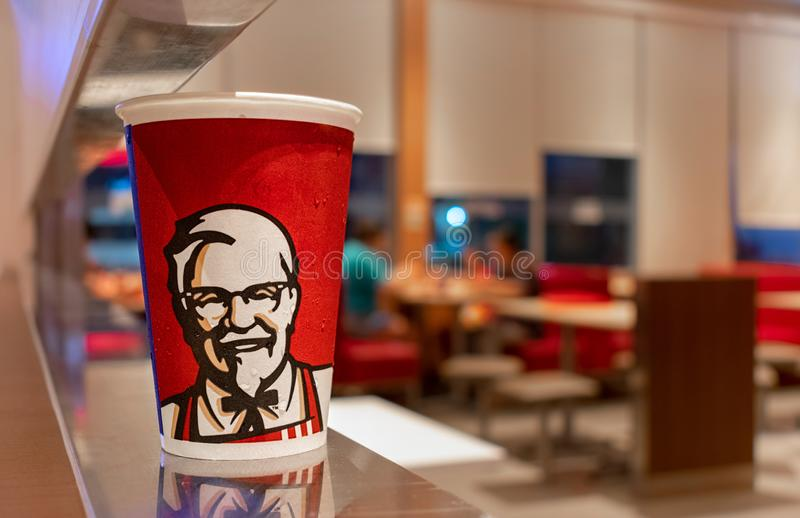 BANGKOK, THAILAND - MARCH 10: Colonel Sander paper soda cup sits on a counter in a KFC fast food restaurant on Petchkasem 69 in. BANGKOK, THAILAND - MARCH 10 stock images