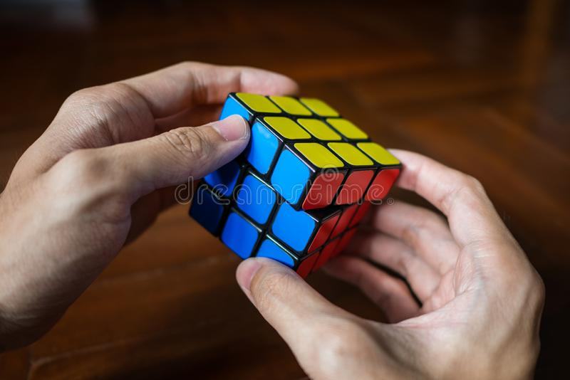A man solving Rubik`s cube. Bangkok, Thailand - March 28, 2018 : A man solving Rubik`s cube stock images