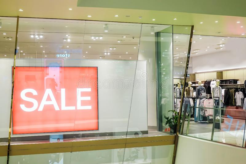 Sales promotion of women and man fashion clothes retail store in shopping mall, sale label sign sticker in front of shop door royalty free stock images