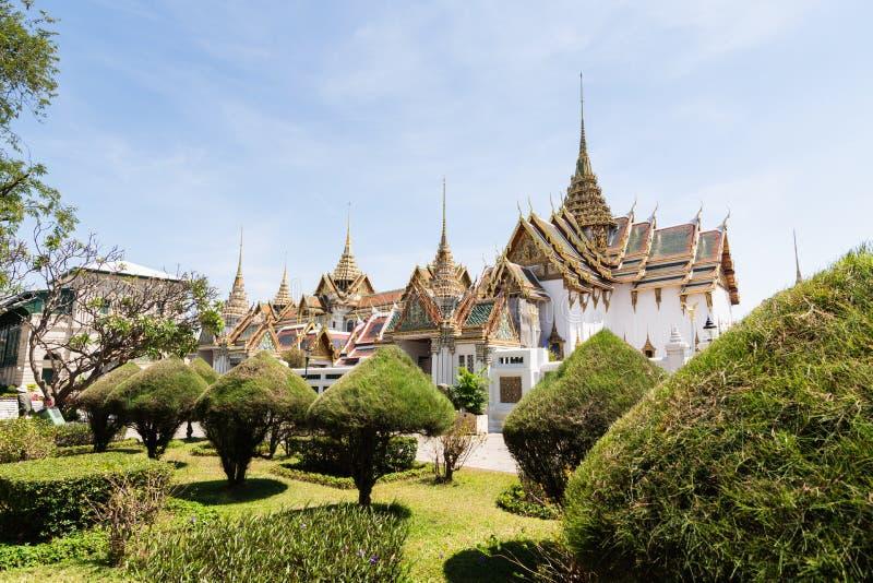 BANGKOK, THAILAND - MARCH 2019: View over Grand Palace and Chakri Maha Prasat hall through the trees and bushes royalty free stock photos