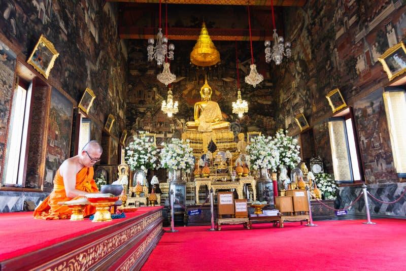 BANGKOK THAILAND - MARS 2019: Buddistisk munk som inom ber av prästvigningkorridor på Wat Arun arkivbild