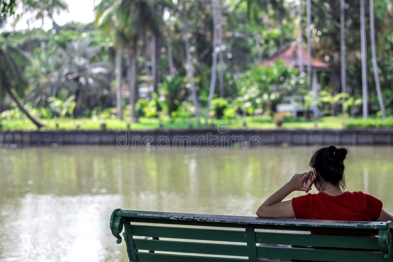 Bangkok Thailand mars 3,2019: Kvinnor som sitter på en mobiltelefon i, parkerar royaltyfri foto