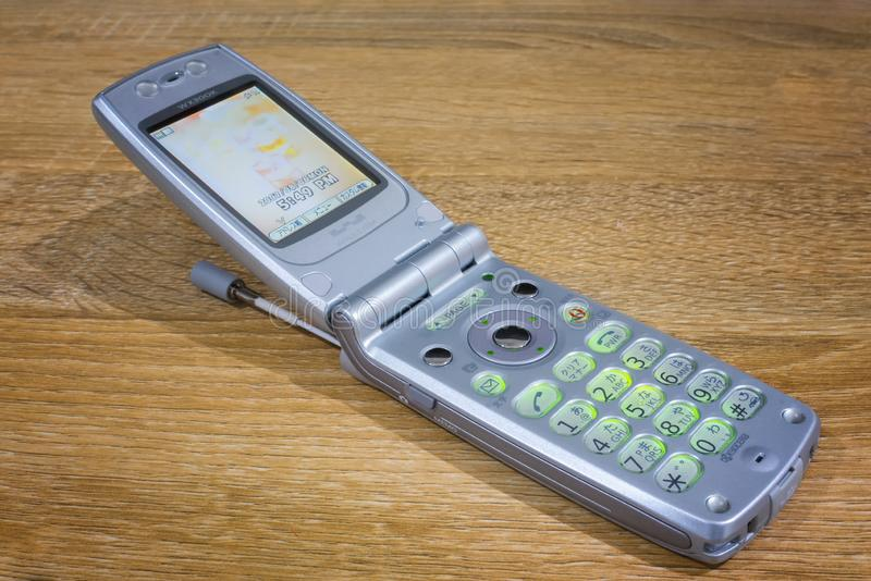 BANGKOK, THAILAND - MAY 05, 2019: Classic Flip Mobile Cell Phone WX300K from Kyocera Powered On on a Desk royalty free stock photography