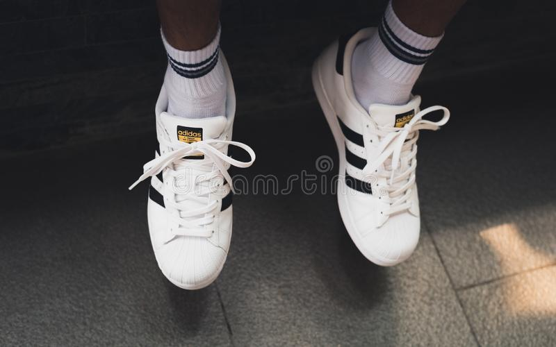 White Adidas Superstar sneakers on men`s feet royalty free stock photography