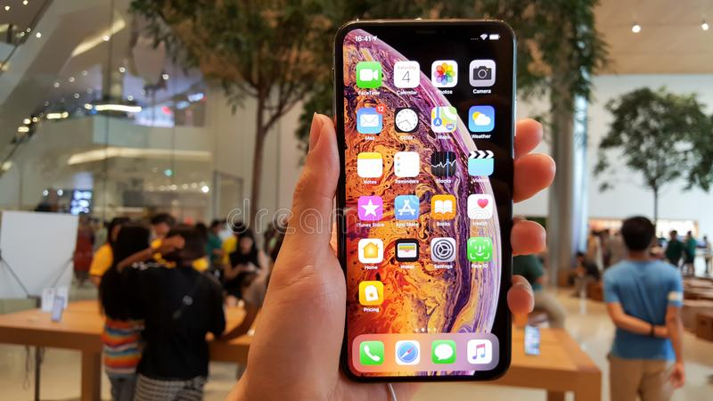 BANGKOK, THAILAND - MAY 6, 2019:  The new Apple iPhone XS Max is displayed with home screen and price list on hand in Apple Store. Iconsiam branch, the first royalty free stock images