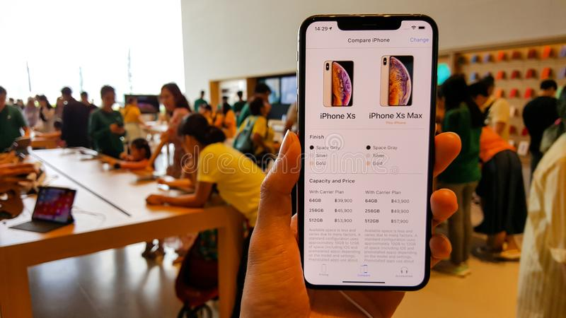 BANGKOK, THAILAND - MAY 6, 2019:  The new Apple iPhone XS Max is displayed with home screen and price list on hand in Apple Store. Iconsiam branch, the first royalty free stock photos