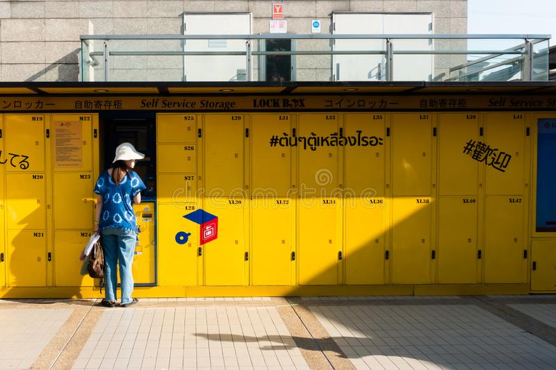 BANGKOK,THAILAND- MAY 19 2019:Travel woman standing in front of service lockers and using Lock box at MRT Chatuchak weekend market. These are electronic self stock photo