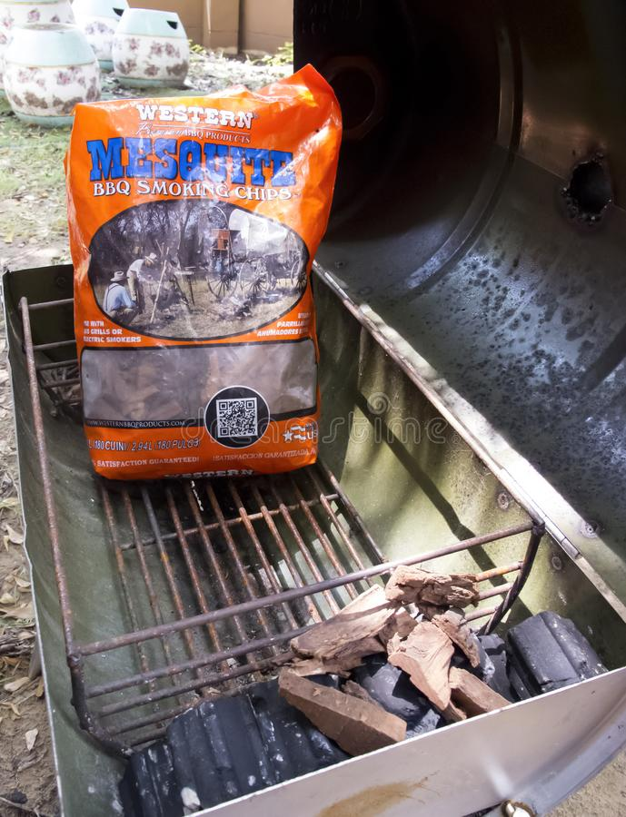 Bangkok, Thailand - May 12, 2018: Western Mesquite BBQ Smoking Chips and Charcoal in Portable Barbecue Grill on back yard stock photography