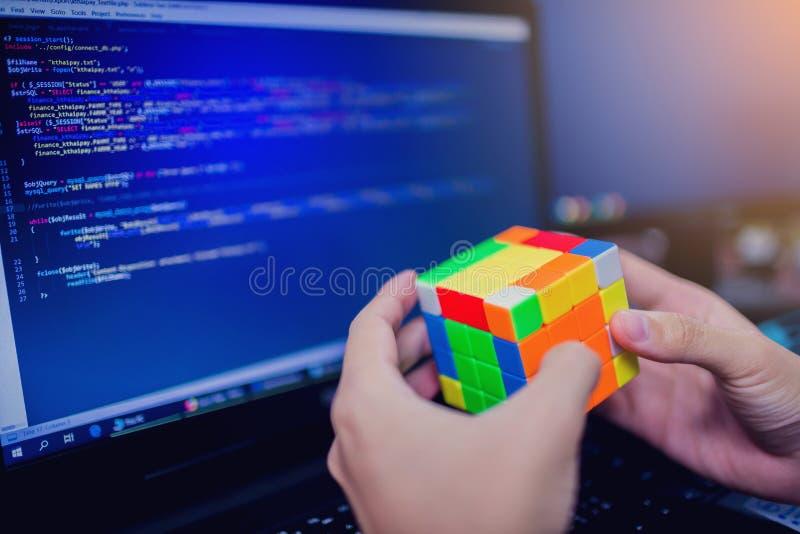 BANGKOK, THAILAND - MEI 15, 2019: De kubus van Rubik van de programmeursholding royalty-vrije stock fotografie