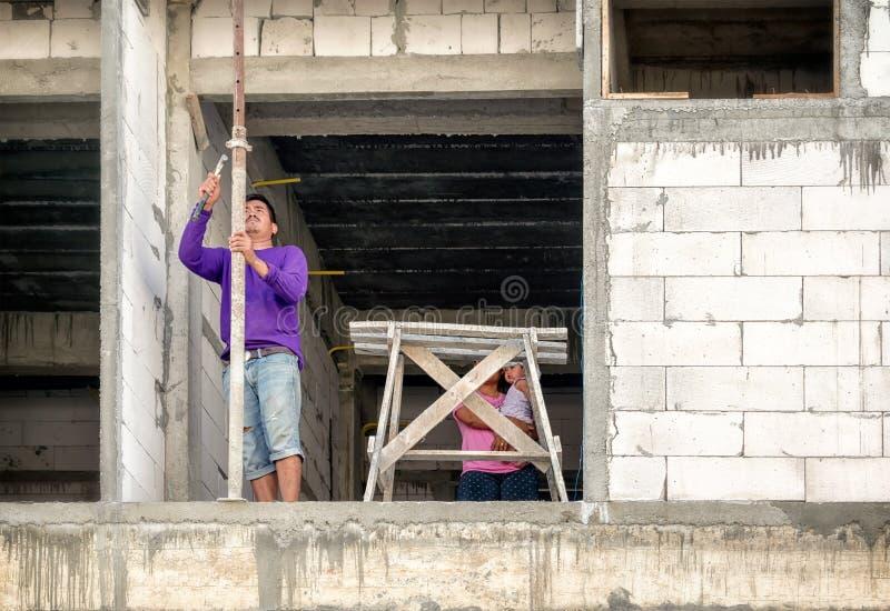 BANGKOK, THAILAND - MEI 05: De niet ge?dentificeerde bouwvakker brengt vrouw en baby om te werken bij de flatbouwwerf bij royalty-vrije stock fotografie