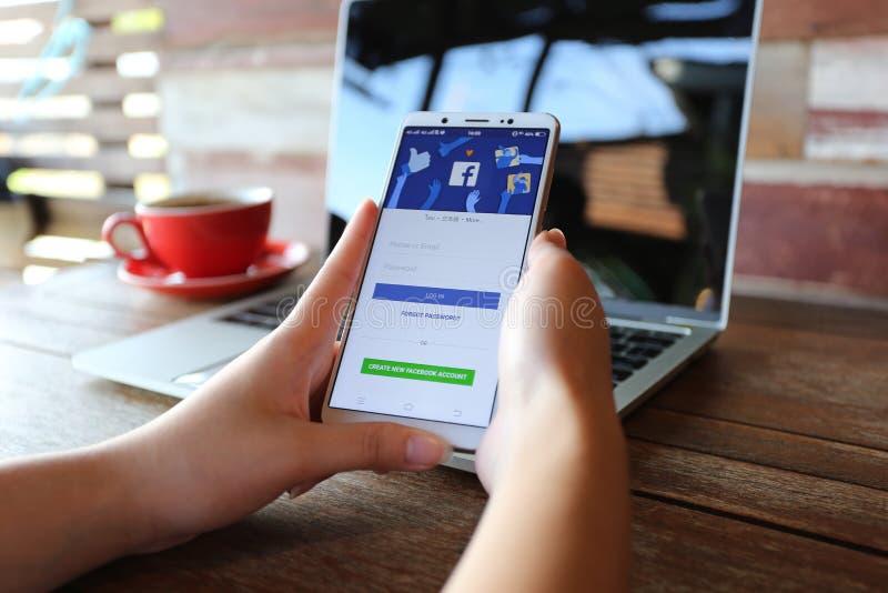 Bangkok, Thailand: Mei 01, 2019, Vrouwenhand die Vivo V7 met de sociale media app gebruiken van Facebook en leidt tot nieuw faceb stock foto's