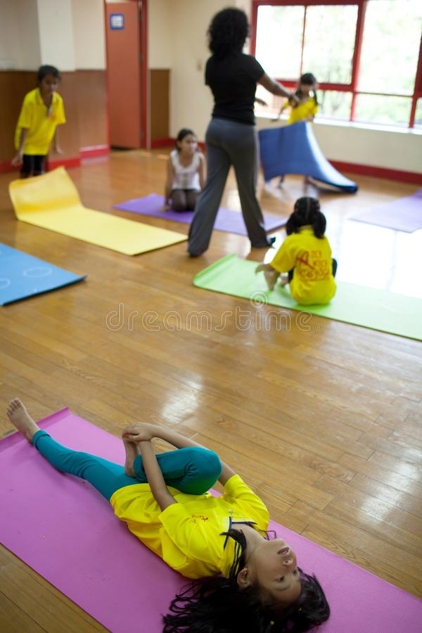 Young children take a yoga class with their teacher. stock images