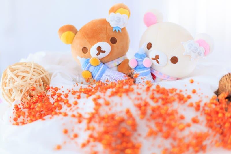 Bangkok, Thailand - November 24, 2018: Cute Rillukkuma Baby Bear Couple Holding Milk Bottle Dolls with decorating beads on white stock images