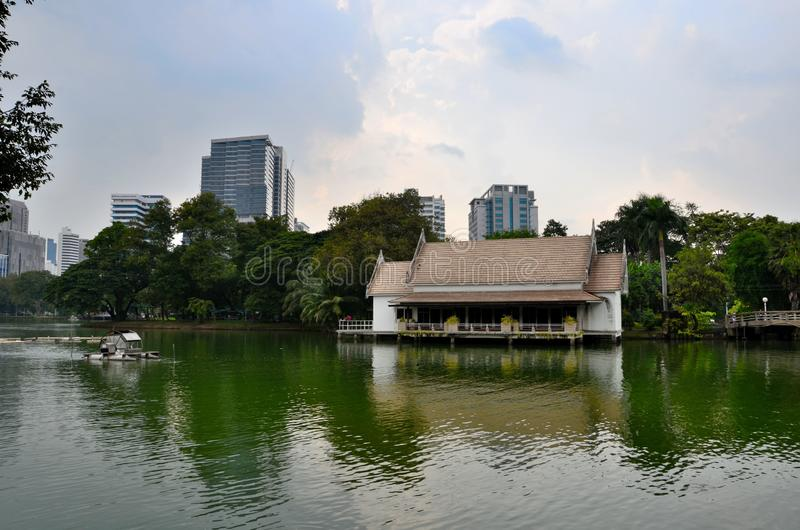Lake and house with skyline at Lumphini Park Bangkok Thailand. Bangkok, Thailand - November 16, 2018: A lake with a lakeside building and a water mill located stock images