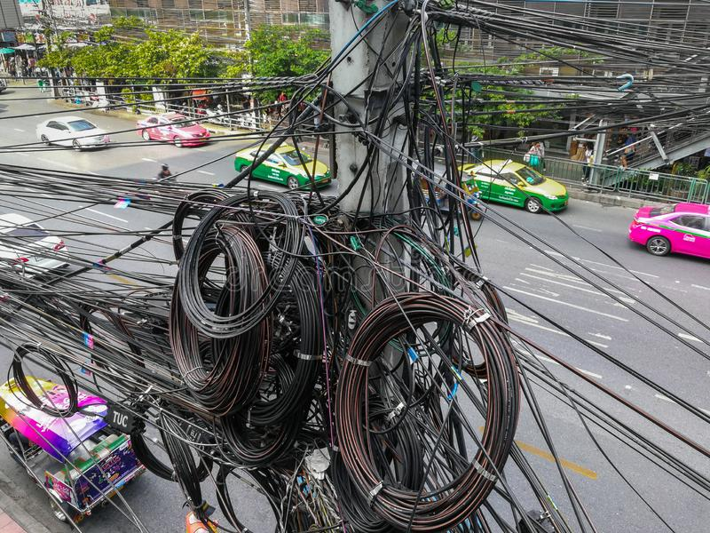 Messy and bizarre telecommunication lines. Bangkok, Thailand - November 29, 2018: Messy telephone line, fiber optic cable, TV cable which all are installed on royalty free stock photo