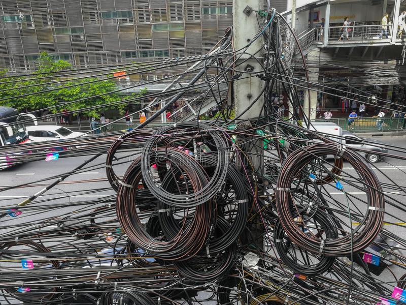 Messy and bizarre telecommunication lines. Bangkok, Thailand - November 29, 2018: Messy telephone line, fiber optic cable, TV cable which all are installed on royalty free stock photography