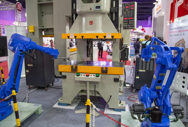 Robotic arm loading metal sheet to stamping press machine royalty free stock images