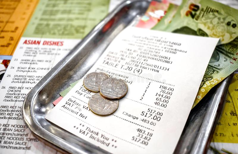 BANGKOK, THAILAND - NOVEMBER 28: Spare Change and receipt from T. Ook Lae Dee international restaurant in Bangkok after paying the bill on November 28, 2017 royalty free stock image