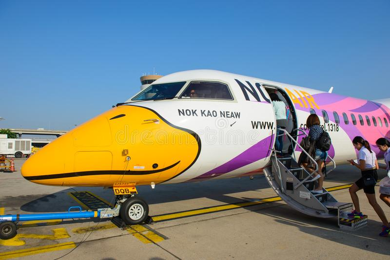 Bangkok, Thailand - November 26, 2014 : Unidentified people walked to BOMBARDIER Q400 NextGen `Nok Kao Neaw` of Nok Air at Don Mu. Eang Airport, Bangkok royalty free stock photos
