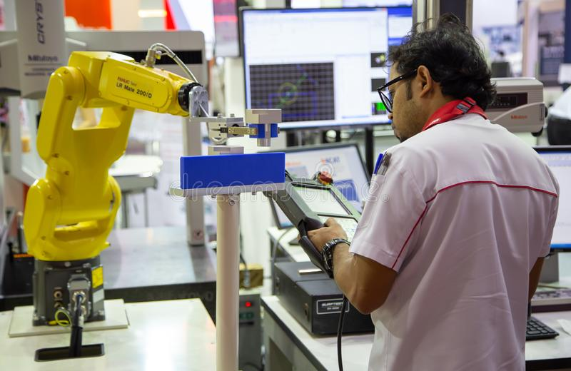 Worker control robot arm to loading and unloading workpiece royalty free stock image