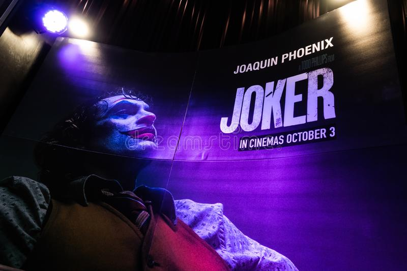 Bangkok, Thailand - Oct 1, 2019: Joker movie backdrop poster with spotlights showing in movie theatre. Cinema promotional advertisement, or film industry stock images